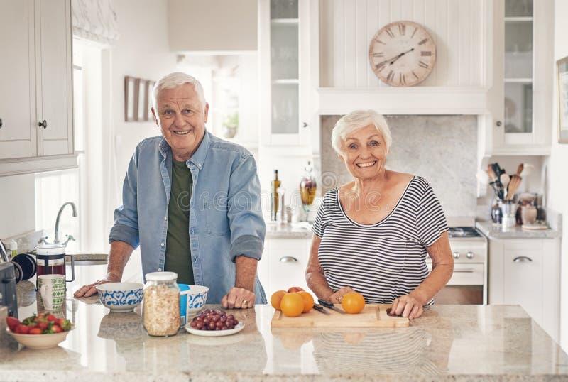 Glimlachende oudsten die een gezond ontbijt samen thuis voorbereiden royalty-vrije stock foto's