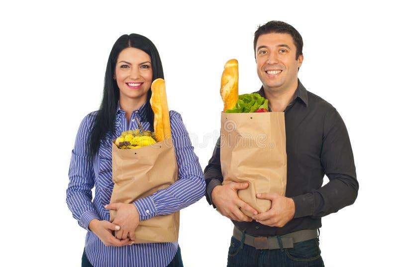 Glimlachende paar het winkelen kruidenierswinkels stock foto's