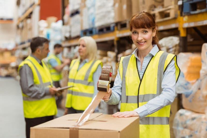 Glimlachende pakhuisarbeiders die een verzending voorbereiden stock afbeelding