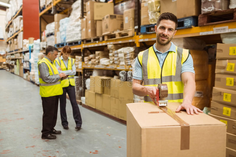 Glimlachende pakhuisarbeiders die een verzending voorbereiden royalty-vrije stock foto