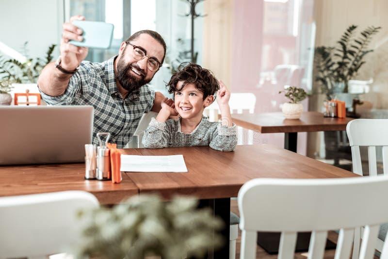 Glimlachende papa die glazen dragen die telefoon houden makend selfie met zoon stock foto