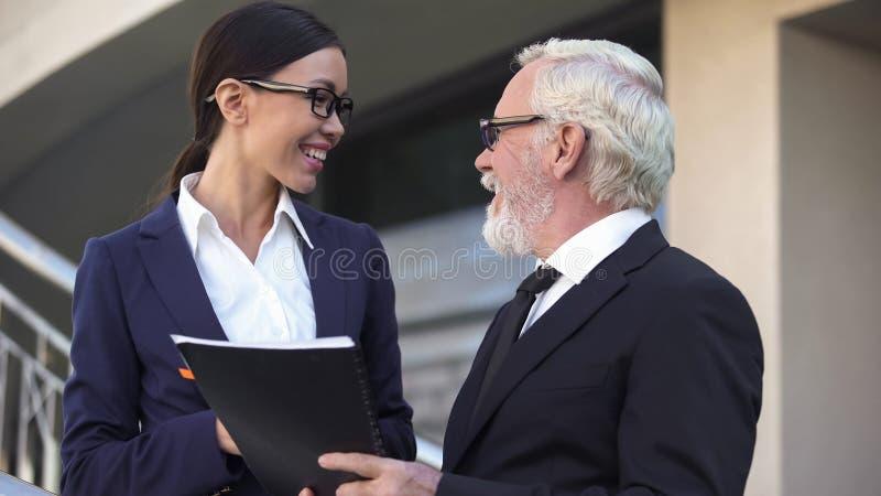Glimlachende partners die elkaar, bedrijfmanager en medewerker kijken stock foto