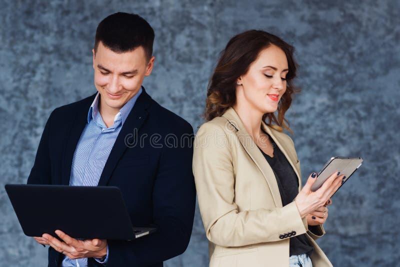 Glimlachende partners die met laptop en tablet tegenover grijze achtergrond werken stock afbeeldingen