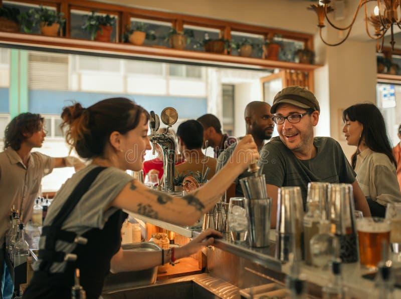 Glimlachende patroon die tot dranken in een in bar opdracht geven stock fotografie