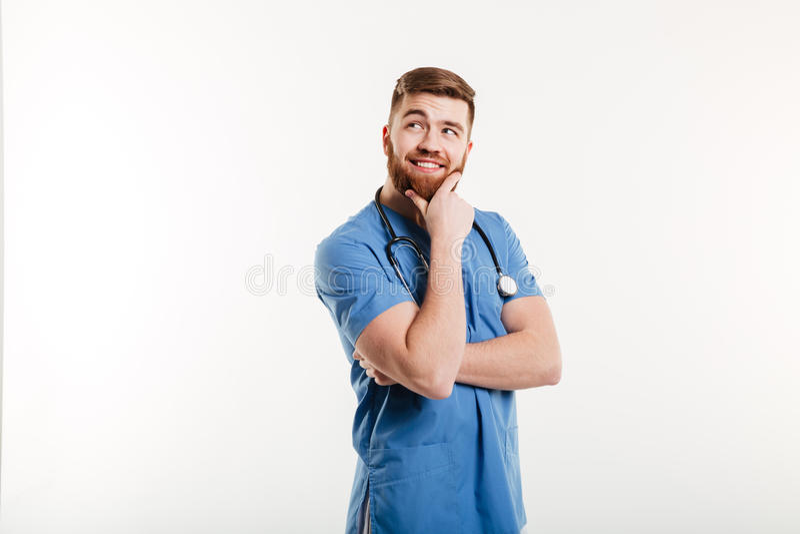 Glimlachende peinzende mannelijke arts die weg met hand op kin kijken royalty-vrije stock foto's