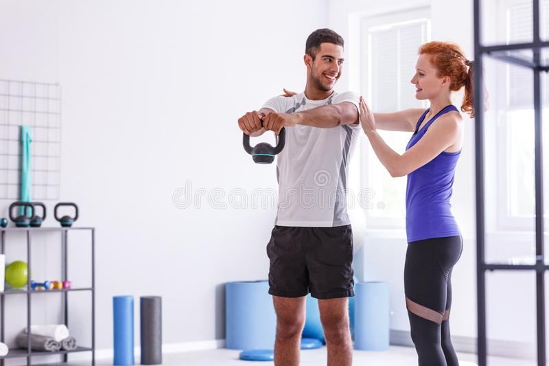 Glimlachende persoonlijke trainer en sportvrouw die met gewicht bij gymnastiek uitwerken stock foto