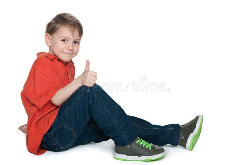 Glimlachende peuterjongen met zijn omhoog duim stock afbeeldingen