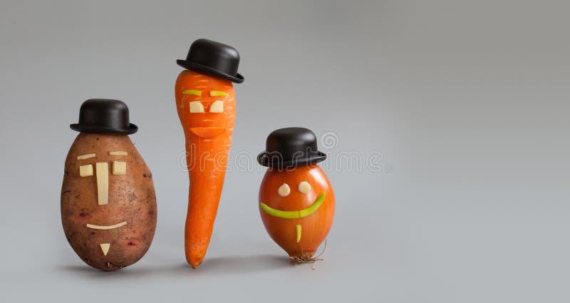 Glimlachende plantaardige karakters Mijnheer aardappel, juffrouwwortel en herenui met grappige gezichten zwarte hoed Veganistfami stock foto's