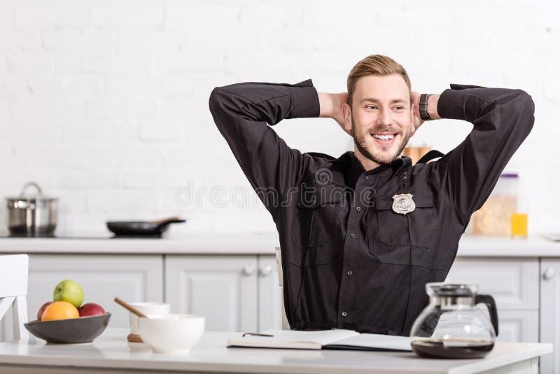 Glimlachende politieman met handen op hoofdzitting stock afbeelding