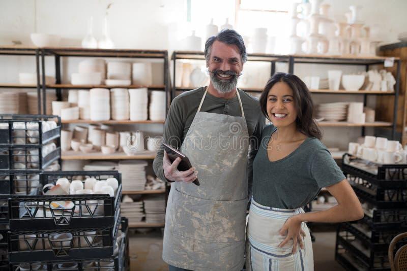 Glimlachende pottenbakkerscollega's die tabletpc met behulp van die camera bekijken royalty-vrije stock fotografie