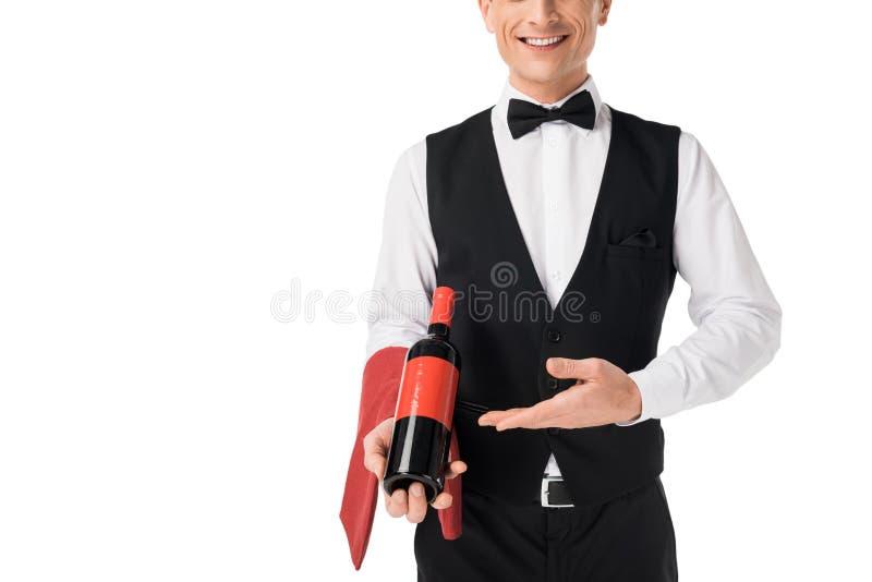 Glimlachende professionele kelner die wijnfles voorstellen stock foto
