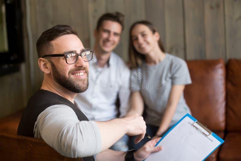 Glimlachende professionele mensenpsycholoog die jong paar raadplegen lo royalty-vrije stock foto