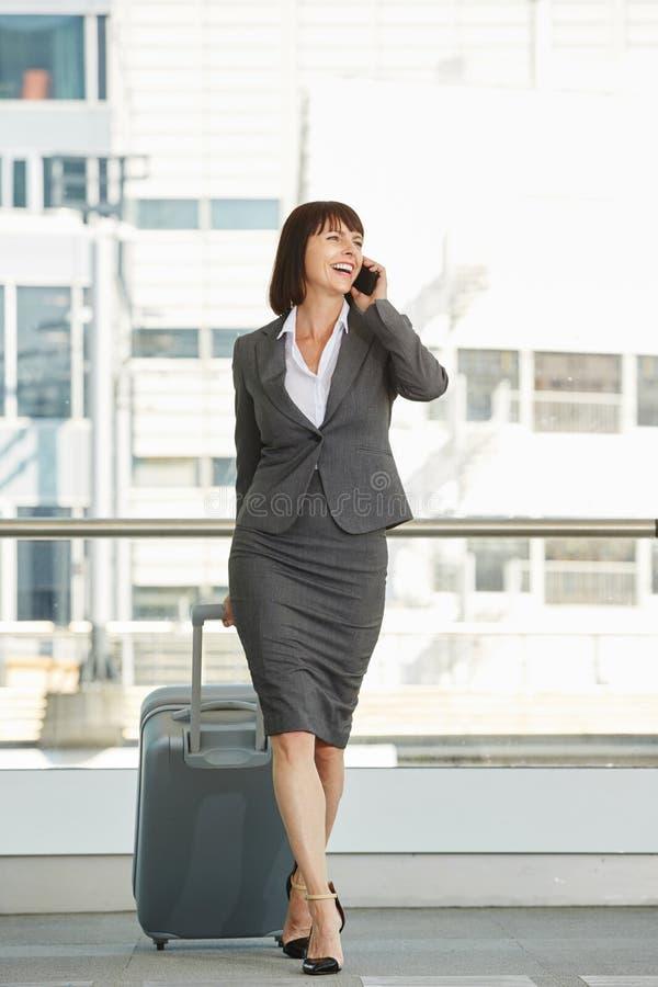 Glimlachende professionele vrouw met koffer en slimme telefoon royalty-vrije stock afbeeldingen