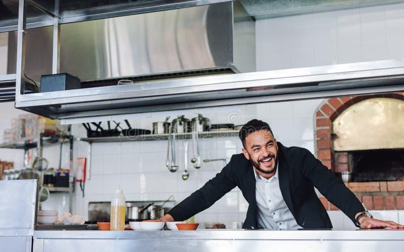 Glimlachende restauranteigenaar die zich bij keukenteller bevinden royalty-vrije stock afbeelding