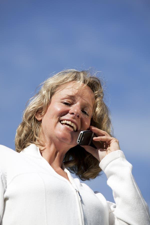 Glimlachende rijpe blonde vrouw met cellphone stock afbeeldingen