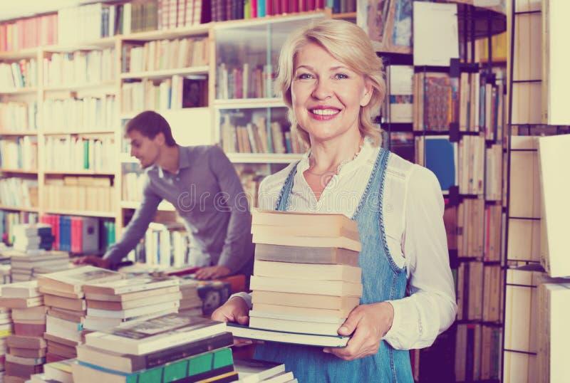 Glimlachende rijpe het boekstapel van de vrouwenholding stock foto's