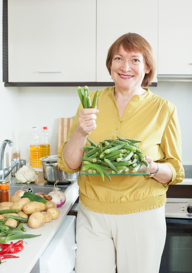 Glimlachende rijpe huisvrouwen kokende groenten stock fotografie