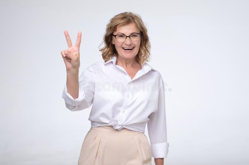 Glimlachende rijpe Kaukasische bedrijfsdame die vredesgebaar doen die twee vingers tonen royalty-vrije stock foto