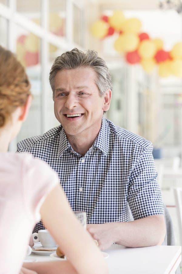Glimlachende rijpe man die aan jonge vrouw bij lijst in restaurant spreken royalty-vrije stock foto