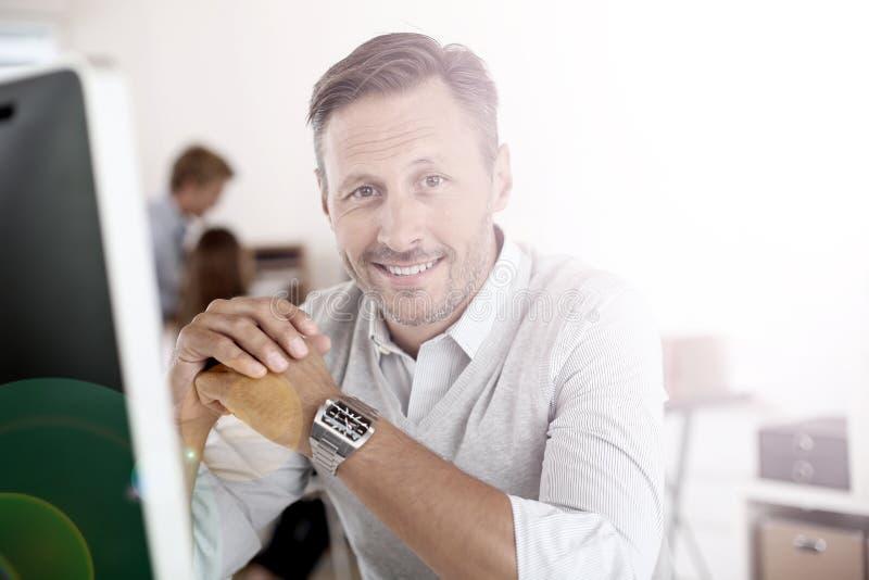 Glimlachende rijpe mens die aan computer werken royalty-vrije stock afbeelding