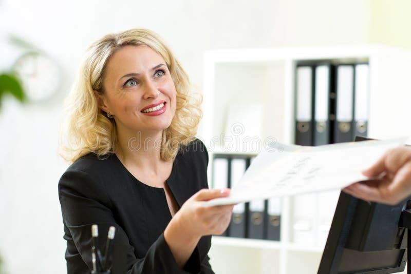 Glimlachende rijpe onderneemster die document geven aan royalty-vrije stock afbeeldingen