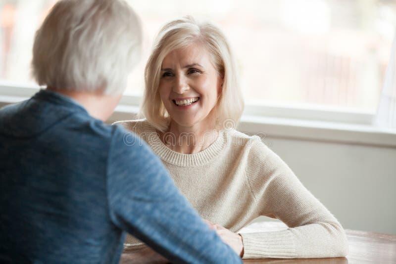Glimlachende rijpe vrouw die aan de mens luisteren die, het oude paar dateren spreken royalty-vrije stock afbeeldingen
