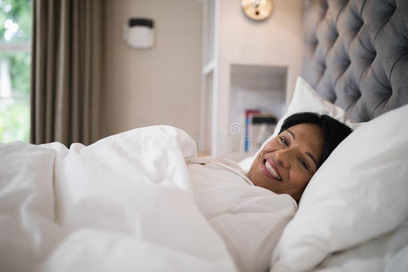 Glimlachende rijpe vrouw die op bed thuis rusten stock foto's