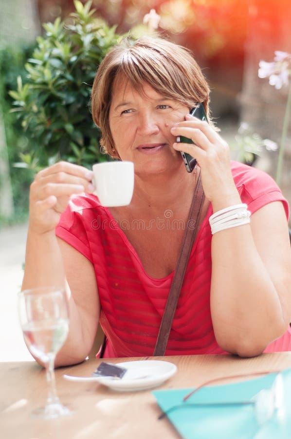 Glimlachende rijpe vrouw die op smartphone en het drinken koffie i spreken stock afbeelding