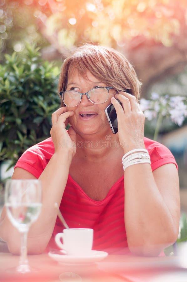 Glimlachende rijpe vrouw die op smartphone en het drinken koffie i spreken stock fotografie