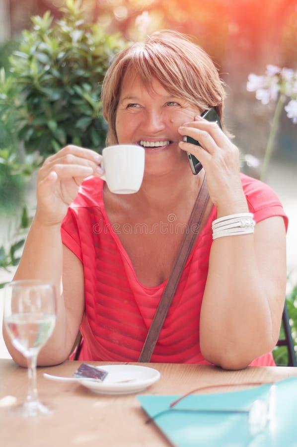 Glimlachende rijpe vrouw die op smartphone en het drinken koffie i spreken royalty-vrije stock afbeeldingen