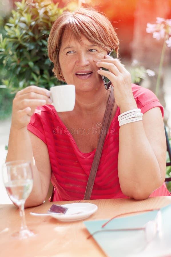 Glimlachende rijpe vrouw die op smartphone en het drinken koffie i spreken stock foto