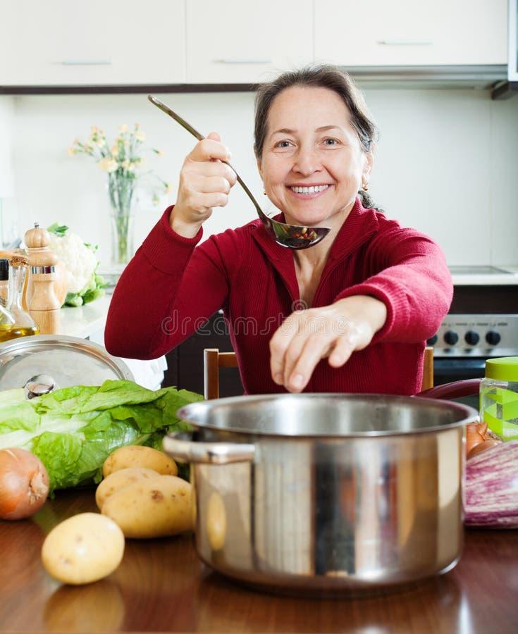 Glimlachende rijpe vrouw die zout toevoegen binnen aan soep stock fotografie