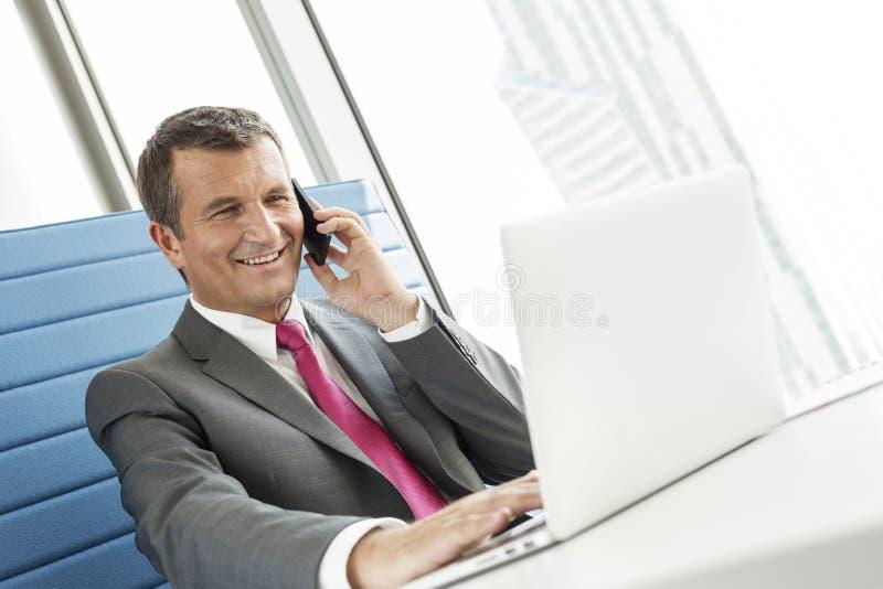 Glimlachende rijpe zakenman die op celtelefoon spreken terwijl het gebruiken van laptop in bureau stock afbeelding