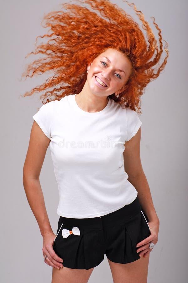 Glimlachende rode haired vrouw met haar het vliegen royalty-vrije stock foto's