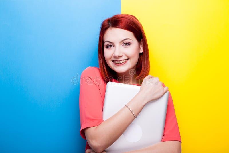 Glimlachende roodharigevrouw met grijze premielaptop in haar handen stock afbeeldingen
