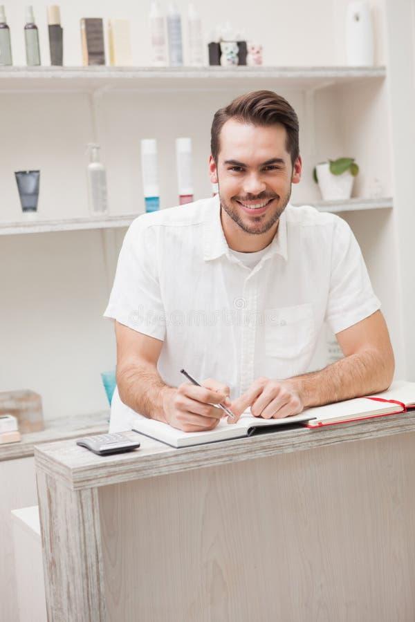 Glimlachende salonarbeider met voorraadboek royalty-vrije stock fotografie