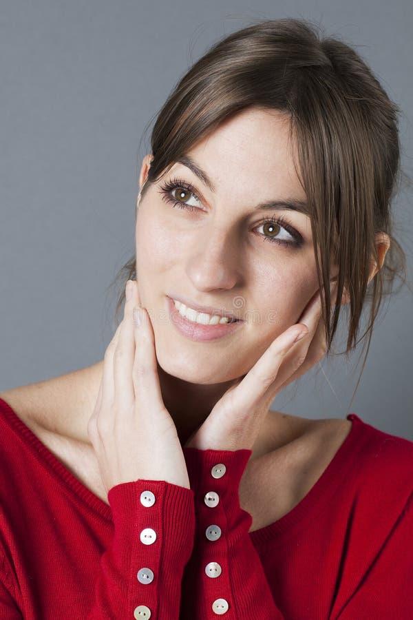 Glimlachende schitterende jaren '20vrouw wat betreft haar gezicht voor zachtheid stock foto's