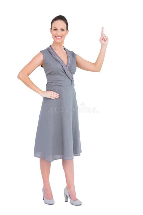 Glimlachende schitterende vrouw die in elegante kleding haar vinger benadrukken stock afbeelding
