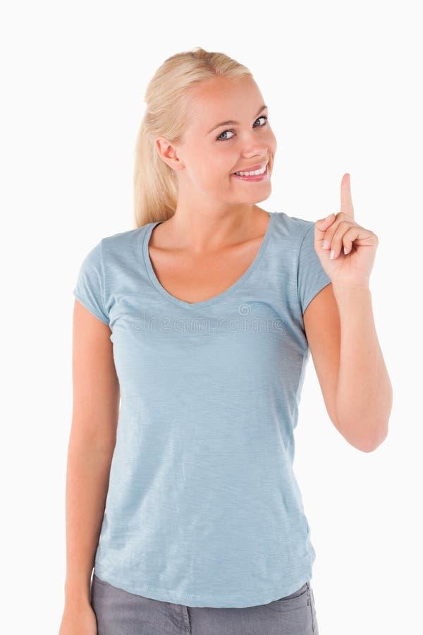 Glimlachende schitterende vrouw die op copyspace richt stock afbeeldingen