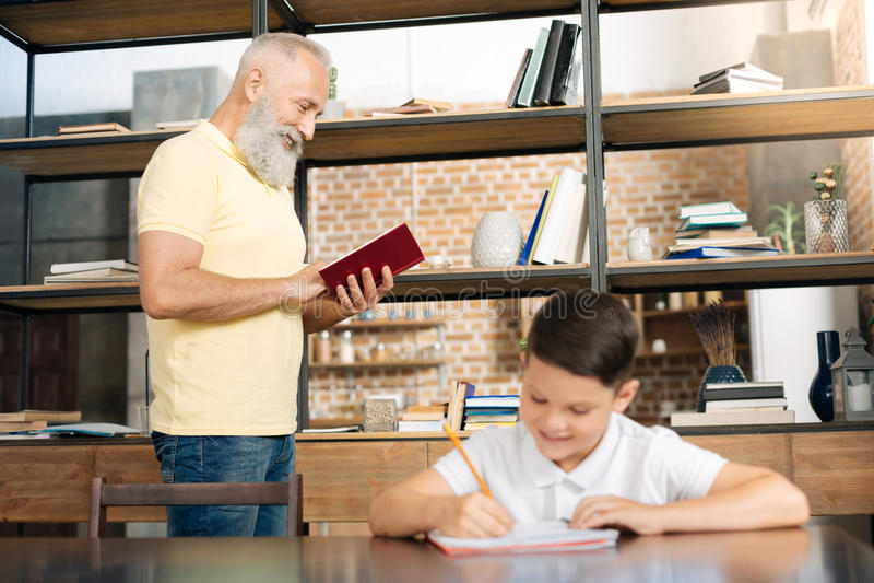 Glimlachende schooljongen die thuiswerk doen terwijl zijn grootvaderlezing stock fotografie