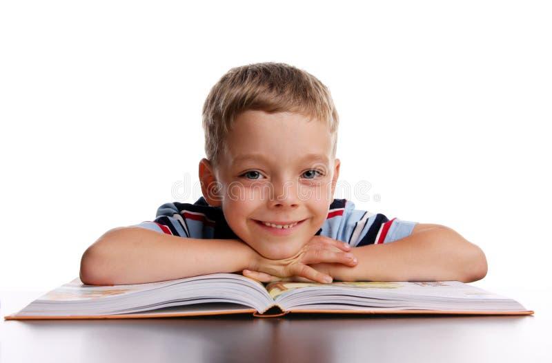 Glimlachende schooljongen met boek stock foto