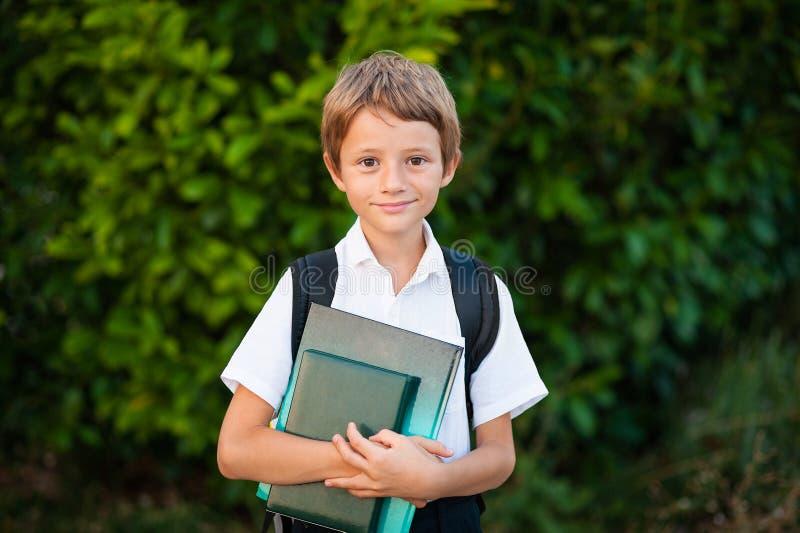 Glimlachende schooljongen met schooltas die in zonnige dag lopen Jongen die van school naar huis gaan stock afbeelding