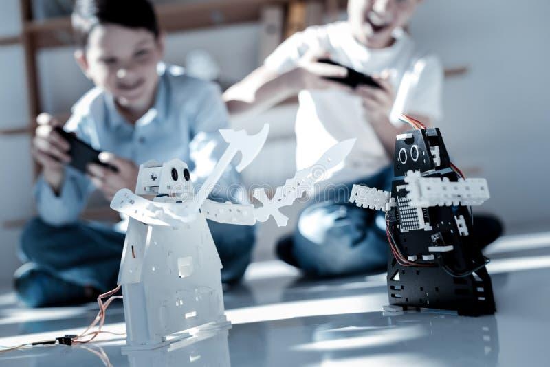 Glimlachende schooljongens die met hun nieuwe robots vechten royalty-vrije stock foto