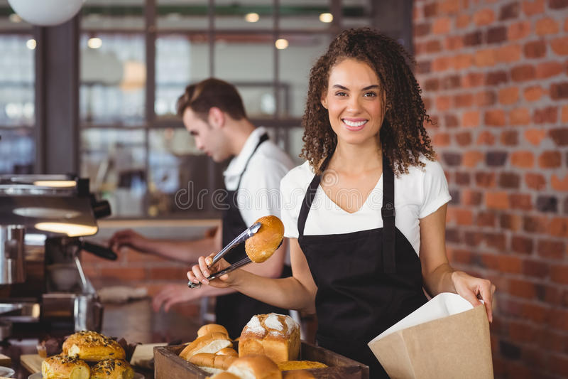 Glimlachende serveerster die broodje in document zak zetten stock afbeeldingen