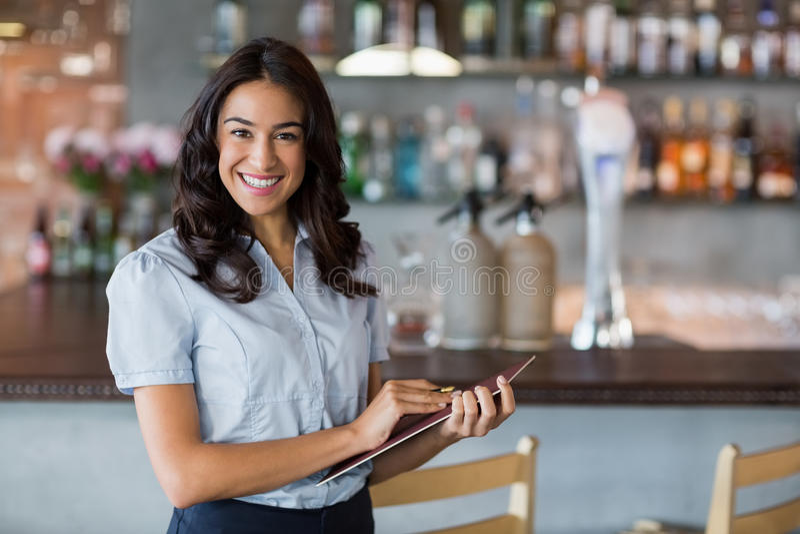 Glimlachende serveerster die een dossier houden royalty-vrije stock afbeeldingen