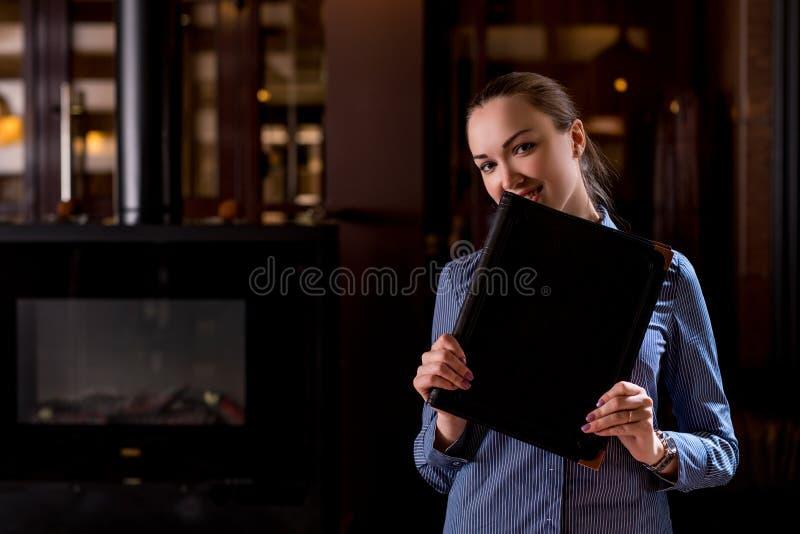 Glimlachende serveerster die haar gezicht achter menu verbergen stock afbeeldingen