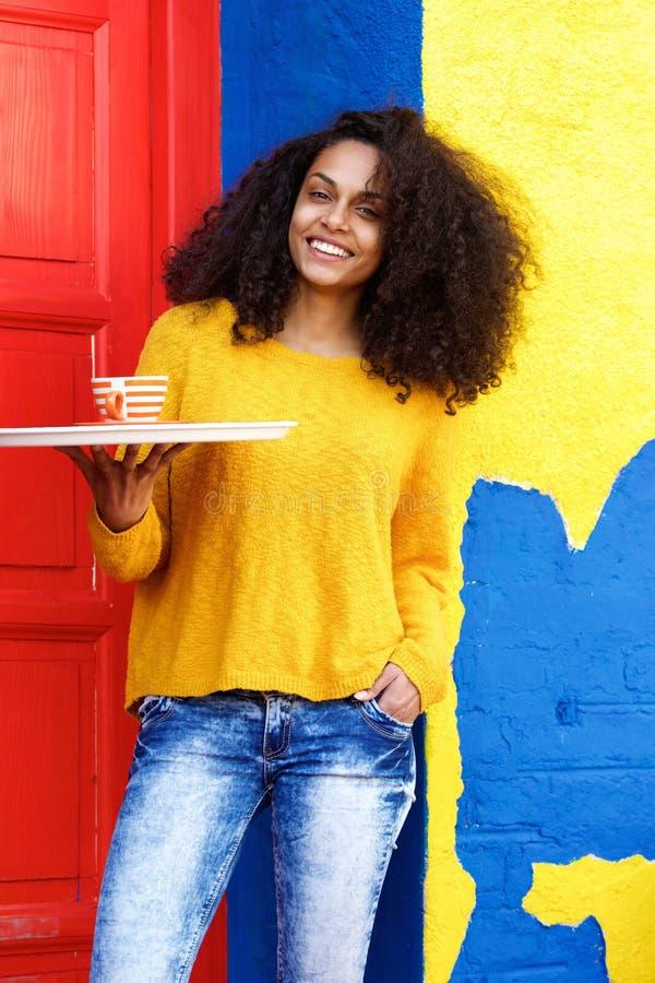 Glimlachende serveerster die koffiekop op een dienblad steunen stock foto