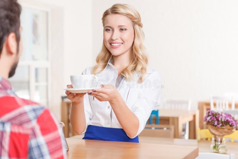 Glimlachende serveerster die kop van koffie geven stock afbeelding