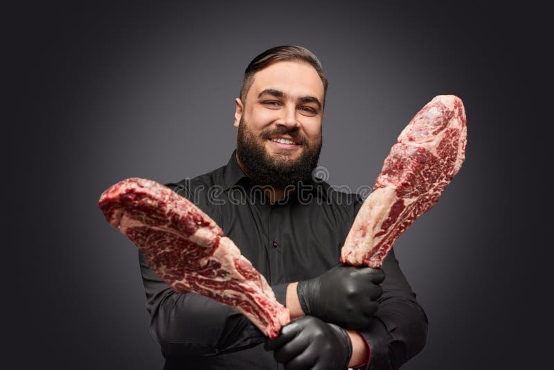 Glimlachende slager met stukken van vlees royalty-vrije stock foto