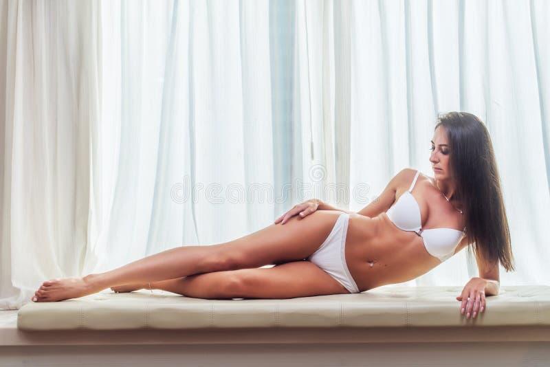 Glimlachende slanke jonge donkerbruine vrouw die witte lingerie dragen die op laag die in camera binnen in lichte ruimte over lig royalty-vrije stock foto